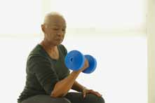 Older Woman Lifting Weights While Sitting